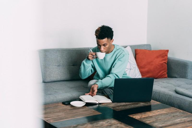 homme bien boit une boisson chaude sur une canapé en regardant son ordinateur