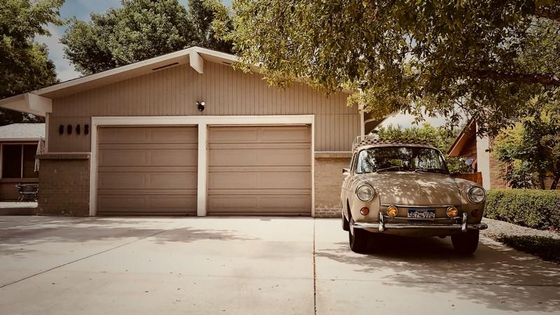 allée d'une maison avec une voiture garée devant le garage