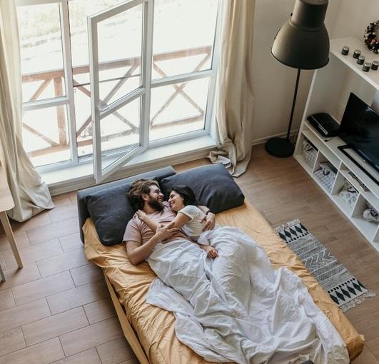 couple dans un lit placé devant une baie vitrée