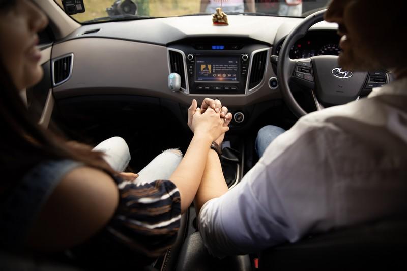 couple qui se tient dans la main dans une voiture