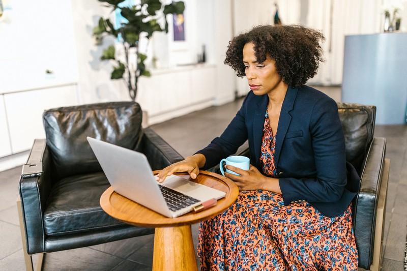 femme assise sur une chaise qui travaille sur son ordinateur