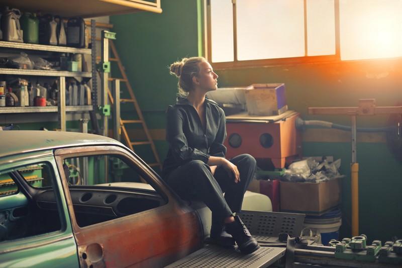 femme dans un garage assise sur une voiture