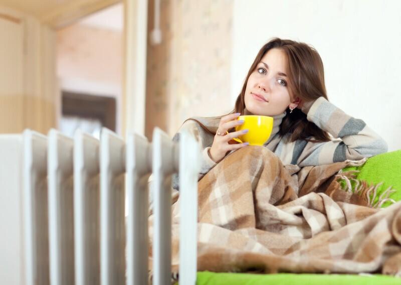 femme qui boit un café devant son radiateur à bain d'huile