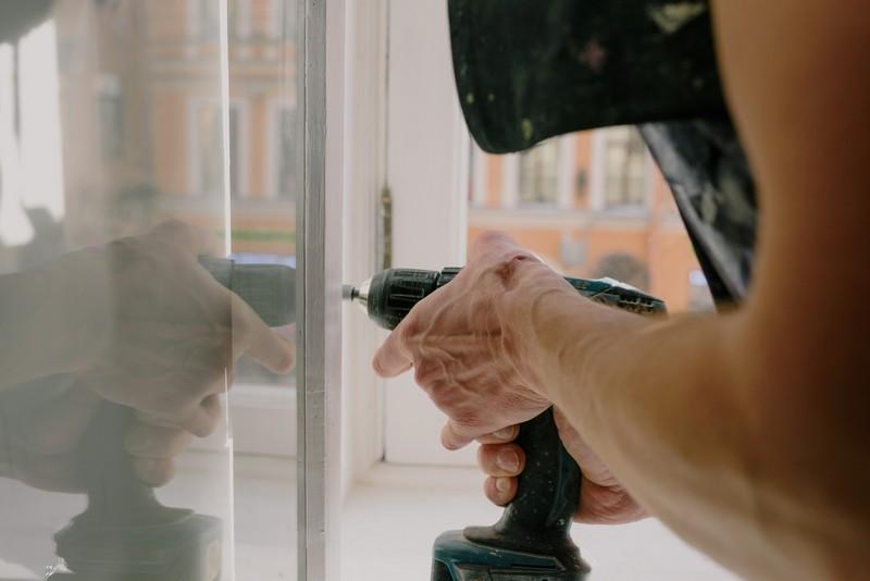 homme qui répare une fenêtre