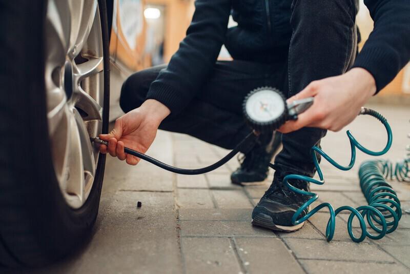 homme qui vérifie la pression des pneus