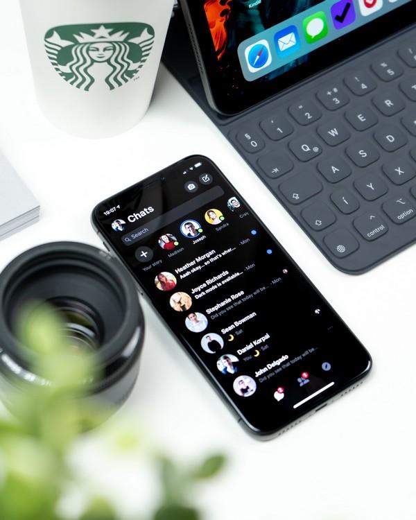 portable posé à côté d'un ordinateur et dont l'application Messenger est ouverte